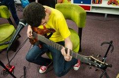 Basowy gitarzysty obsiadanie bawić się jego instrument obrazy royalty free