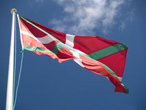 Basque Flag fluttering in the wind. Basque Flag fluttering in blue cloudy sky stock photography