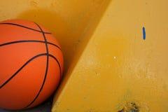 Basquetebol alaranjado que encontra-se sob a parede amarela Fotografia de Stock