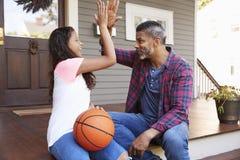 Basquetebol de And Daughter Discussing do pai no patamar da casa fotos de stock royalty free