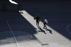 Basquetebol do jogo de duas crian?as em um campo de esportes da rua foto de stock