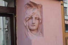 basrelief av kvinnors huvud p? fasaden av byggnaden i Petersburg royaltyfri bild