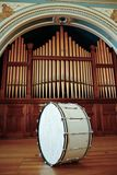 Bass Drum. Large Bass Drum sitting on stage in front of Pipe Organ Stock Image