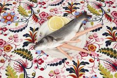 Fish flower plate cannibal doll. A bass fish with arms and legs of a doll inside on a flower plate. Cannibalism and anthropomorphism on a floral fabric patterned Stock Photography