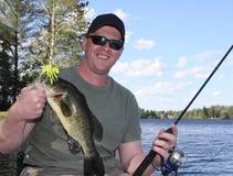Bass fishing. Bass fisherman holding largemouth bass in a boat Stock Photo