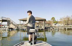 Bass fishing in bass boat on the lake. Dipping lure chartreuse color dye teen man stock image