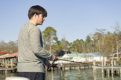 Bass fishing in bass boat on the lake. Dipping lure chartreuse color dye teen man stock images