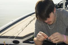 Bass fishing in bass boat on the lake. Dipping lure chartreuse color dye teen man stock photo