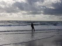 Bass fishing. A lone angler who is surf fishing for bass on a typical storm beach Royalty Free Stock Photography
