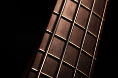 Bass fret board. Detail of the fret board of a bass guitar, on a dark background Royalty Free Stock Images
