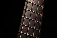 Bass fret board. Detail of the fret board of a bass guitar, on a dark background Stock Photography