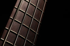 Bass fret board. Detail of the fret board of a bass guitar, on a dark background Royalty Free Stock Photo