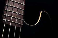 Bass fret board. Detail of the fret board of a bass guitar, on a dark background Royalty Free Stock Photography