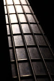 Bass fret board. Detail of the fret board of a bass guitar, on a dark background Stock Photo