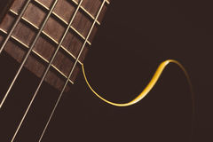 Bass fret board. Detail of the fret board of a bass guitar, on a dark background Stock Images