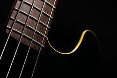 Bass fret board. Horizontal detail of the fret board of a bass guitar, on a dark background Royalty Free Stock Image