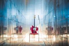 Bass-Gitarre, die auf Stuhl sitzt Lizenzfreie Stockfotografie