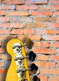 Bass Guitar. Top Of A Bass Guitar Against Brick Wall (area for text royalty free stock photography
