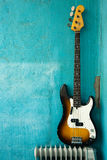 Bass guitar. Guitar on blue background, bass on grunge wall stock photography