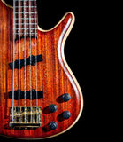Bass guitar. From red textured wood with five strings close up isolated on black background royalty free stock images