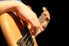 Bass Guitar. A bass guitar player plucks the strings royalty free stock photos