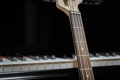 Bass guitar against grand piano keys Stock Photography