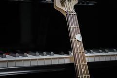 Bass guitar against grand piano keys Royalty Free Stock Photography