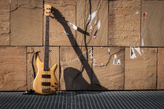 Bass guitar against a wall. Bass guitar against a stone wall Stock Photos