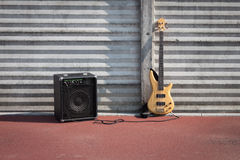 Bass guitar and amplifier against a wall Royalty Free Stock Image