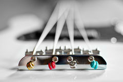 Bass guitar bridge with colorful ball-end strings. Royalty Free Stock Image
