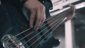 Bass guitar close-up during the performance of the bass composition. Visible strings and hands. Beautiful lighting stock footage