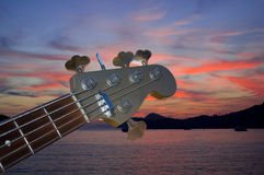 Bass guitar in the dusk. Bass guitar play in the dusk on the red sky and sea royalty free stock photography