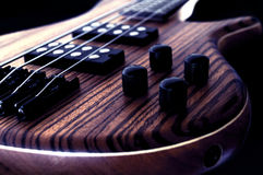 Rock Bass Guitar. Electric Bass wooden gear detail, dark backround Royalty Free Stock Images