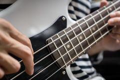 Bass guitar finger style closeup. Musical instruments - concept musical composition and creativity Stock Images