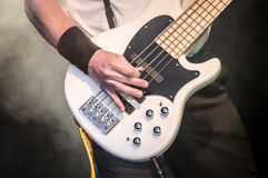 Bass guitar. Hand of a musician playing a five string bass guitar royalty free stock photos