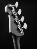 Bass guitar headstock. Black and white photo of a bass guitar headstock over black background Stock Photography