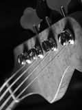 Bass guitar headstock closeup. Black and white photo of a bass guitar headstock over black background Stock Photography