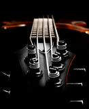 Bass guitar headstock view (low key, shallow depth of field) Royalty Free Stock Photos