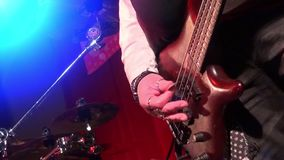 Bass guitar in live action at a concert - rack focus - close up. Playing bass - band playing on rock concert stock video