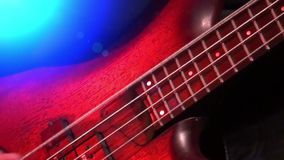 Bass guitar in live action at a concert - rack focus - close up. Playing bass - band playing on rock concert stock video footage