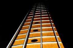 Bass guitar neck four strings with a black background. Four string bass guitar neck with black background royalty free stock photo