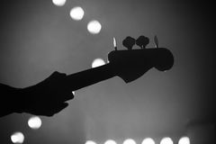 Bass guitar over blurred stage lights. Live music background, electric bass guitar over blurred stage lights, close-up black and white silhouette photo with soft stock photography