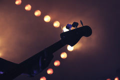 Bass guitar over bright blurred lights. Live rock music background, electric bass guitar over bright blurred stage lights, close-up silhouette photo, soft Stock Images