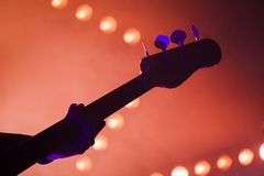 Bass guitar over bright blurred stage lights. Electric bass guitar player over bright blurred stage lights, close-up silhouette photo with soft focus stock photo