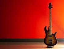 Bass Guitar på en röd bakgrund Arkivbilder