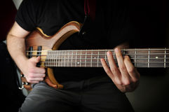 Bass Guitar Player. Man Playing Bass Guitar Inside The Studio stock photography