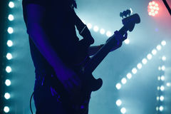 Bass guitar player in blue stage lights Royalty Free Stock Photos