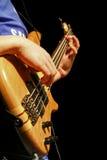 Bass Guitar Player Portrait. Portrait shot of a bass guitar player's guitar isolated on black Royalty Free Stock Photography