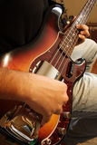 Bass Guitar Player Practice. Closeup of a young bassist playing a fender sunburst bass in he's room stock photo