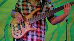 Bass guitar player on stage of ethnic open air concert. Close up shot - male bassist hands playing bass guitar on stage of ethnic open air concert. Entertainment stock video footage